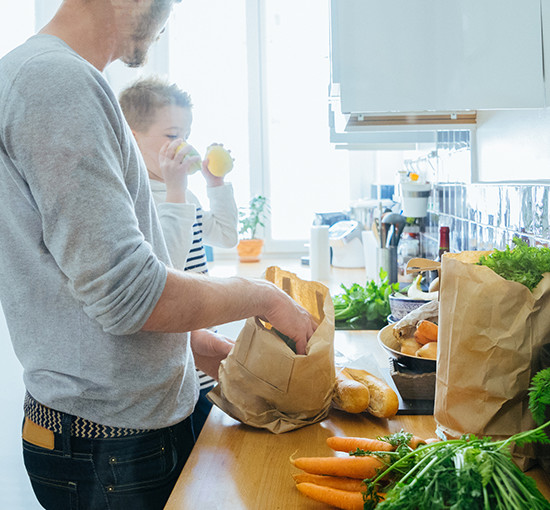 Father and child unpacking groceries in kitchen at home
