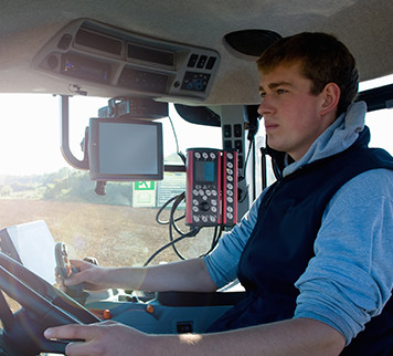 Farmer in a tractor cab with electronic displays